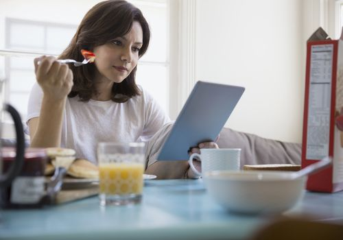 Brunette woman using digital tablet at breakfast table