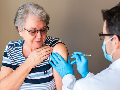 Older woman getting injected with a vaccine by doctor in upper arm