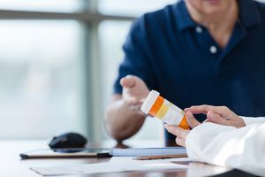 Unrecognizable pharmacist discusses medication with patient