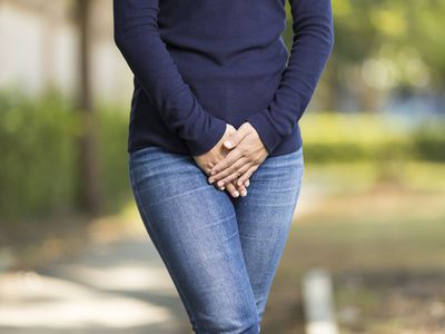 Woman with overactive bladder holding her crotch