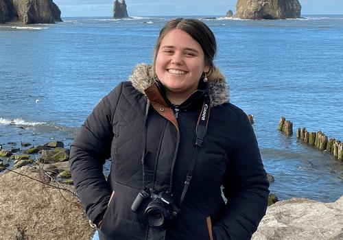 Paola de Varona standing by ocean with camera.