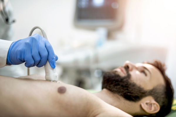 Sick mid adult man having his chest examined by ultrasound technology.