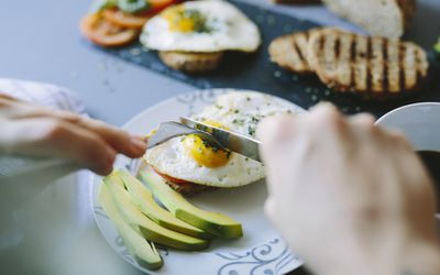 person cutting eggs on toast with avocado
