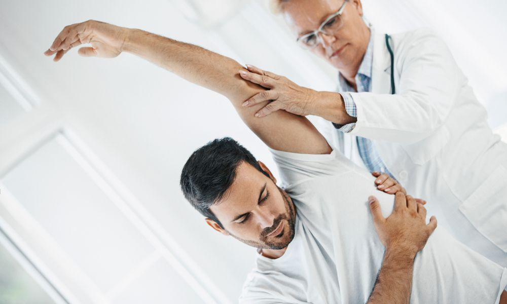 Photo of a doctor examining a man's shoulder.