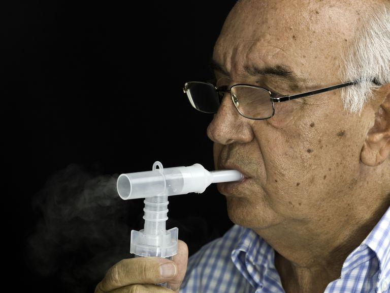 senior man using nebulizer