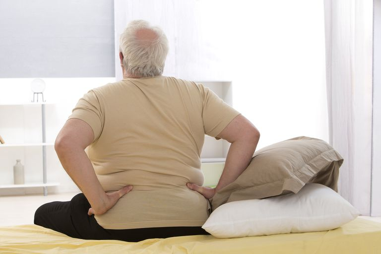 Overweight senior man with back pain