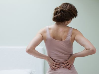 A woman experiencing back pain.
