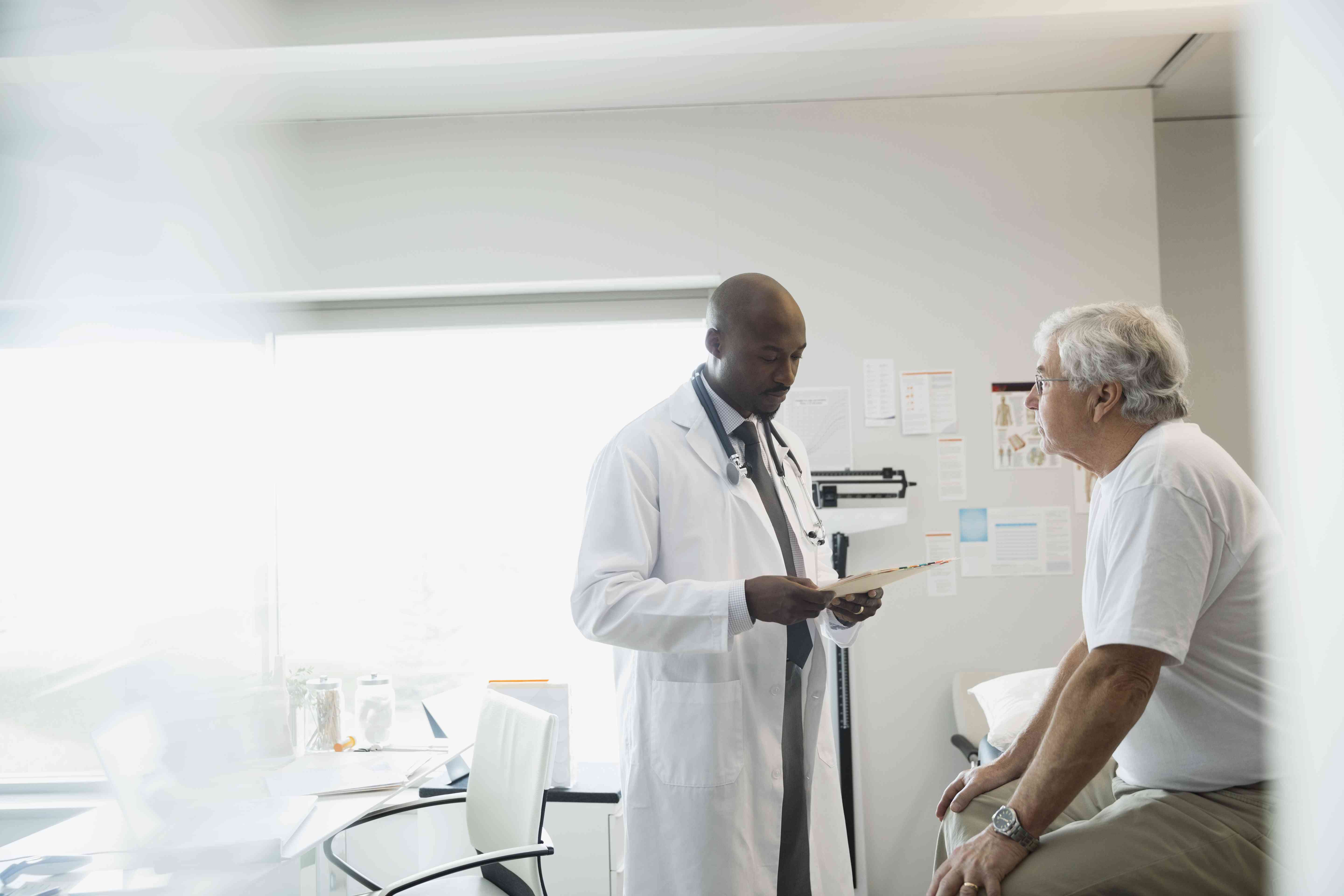 Doctor reviewing medical chart with older man