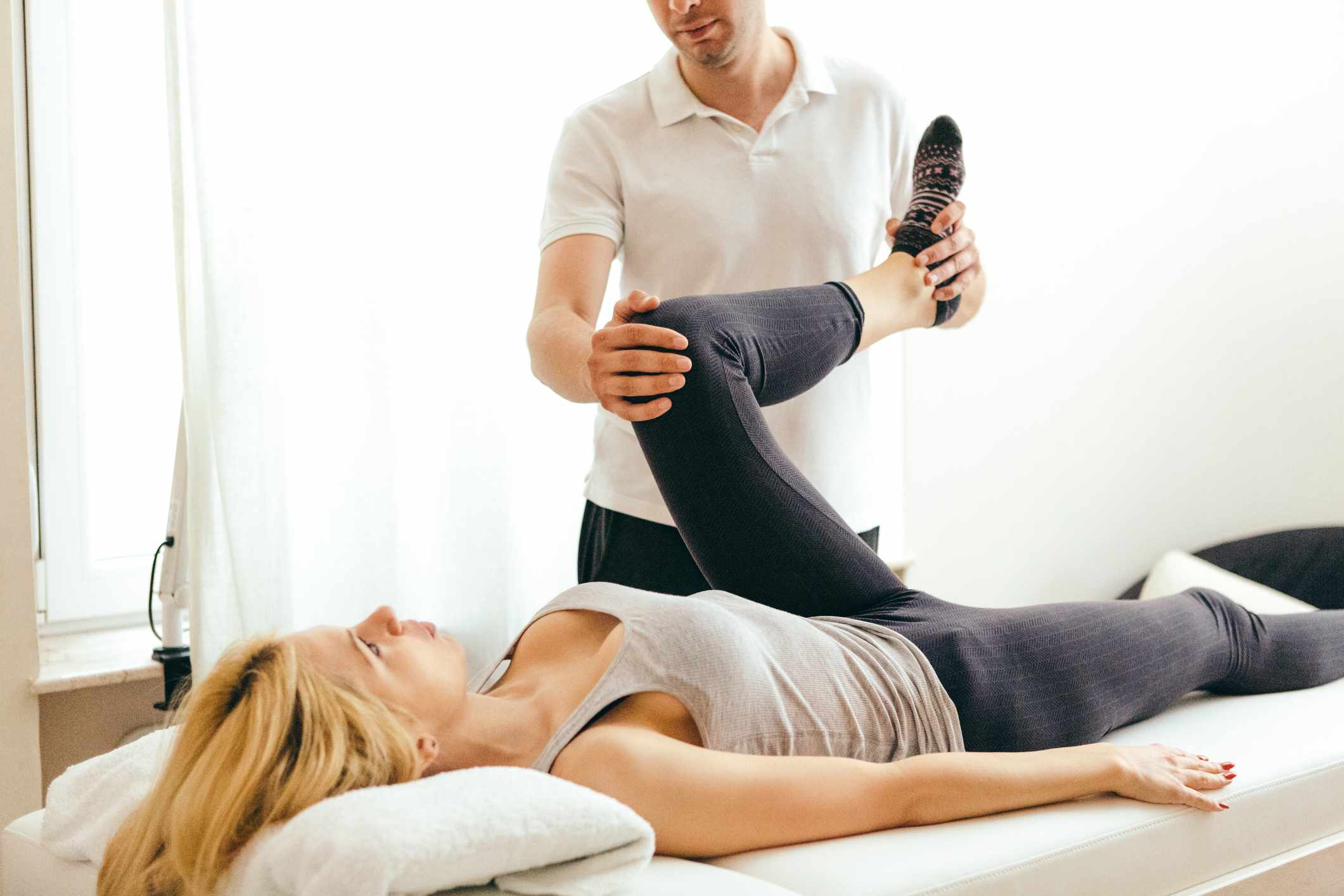 physical therapist assessing a patient's hip mobility