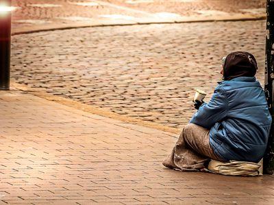 Full Length Rear View Of Woman Begging On Sidewalk
