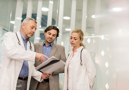 Doctors cooperating with a businessman while working on paperwork.
