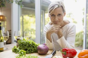 woman leaning on kitchen counter next to vegetables