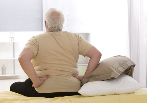 Photo of an overweight man with low back pain sitting on the edge of his bed.