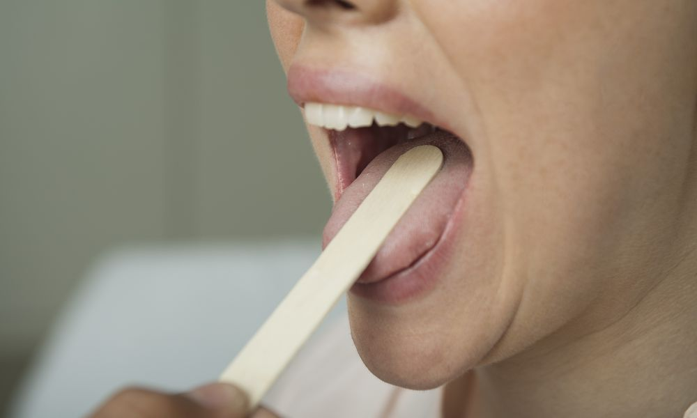Woman having mouth examined with tongue depressor, cropped
