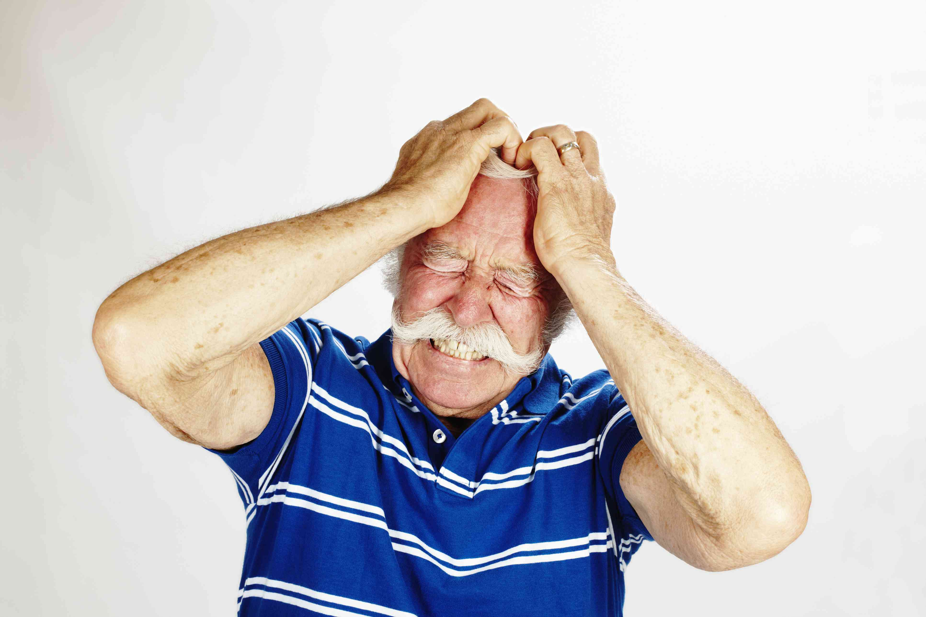 Older man standing against a white background holding his hands on his head while wearing a pained expression