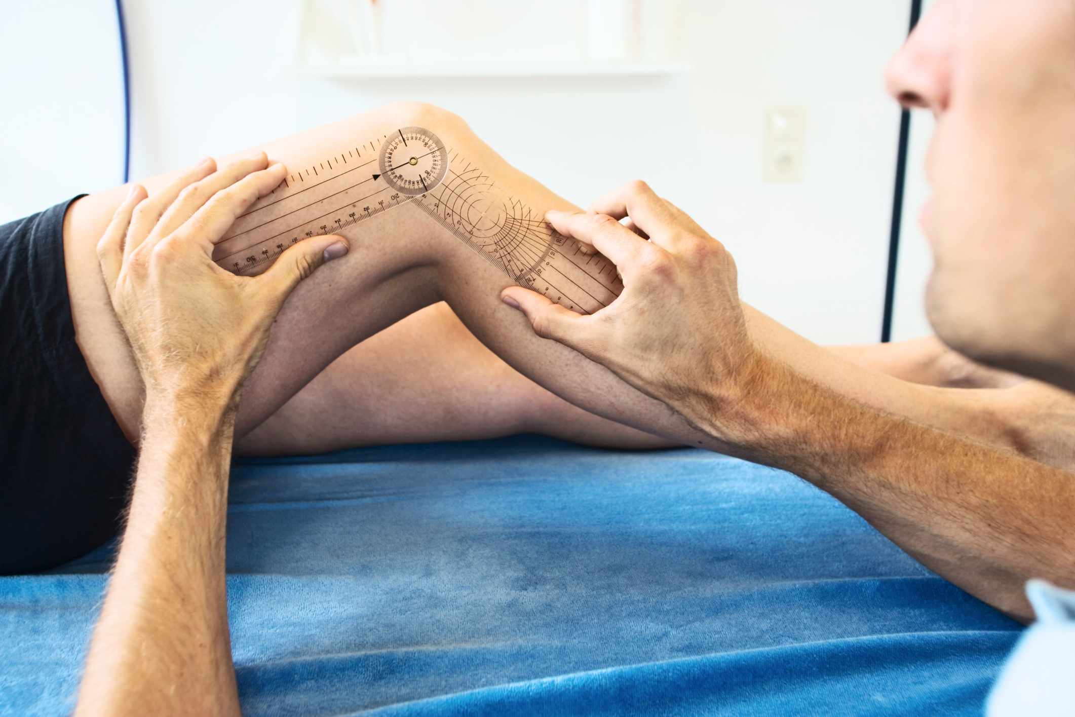 A doctor measuring a knee joint's range