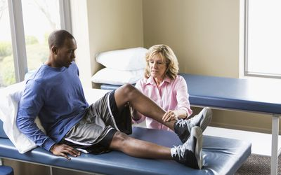 Physical therapist examining patient - stock photo