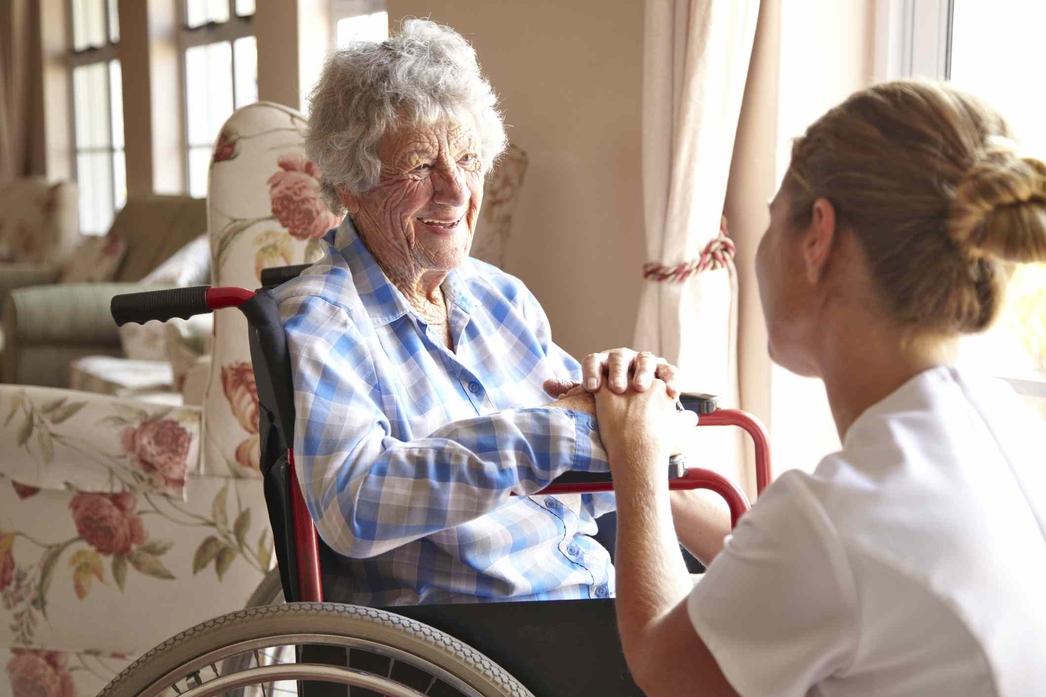 An elderly woman talking to her nurse
