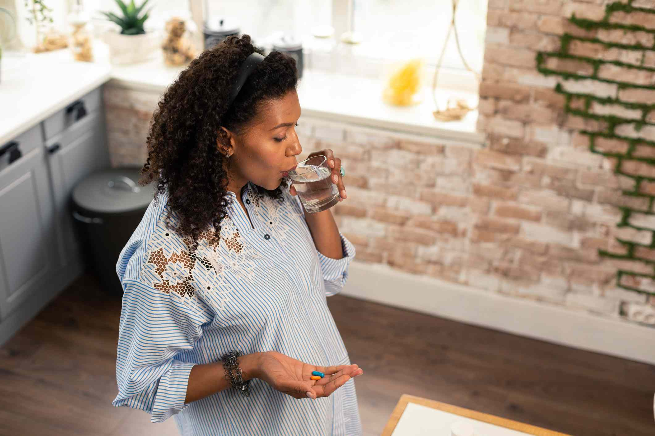 Pregnant person taking prenatal vitamins
