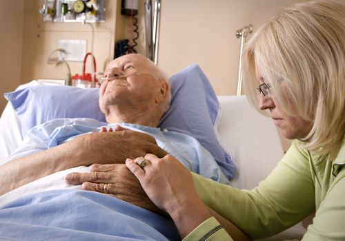 Woman sitting at a man's hospital bedside