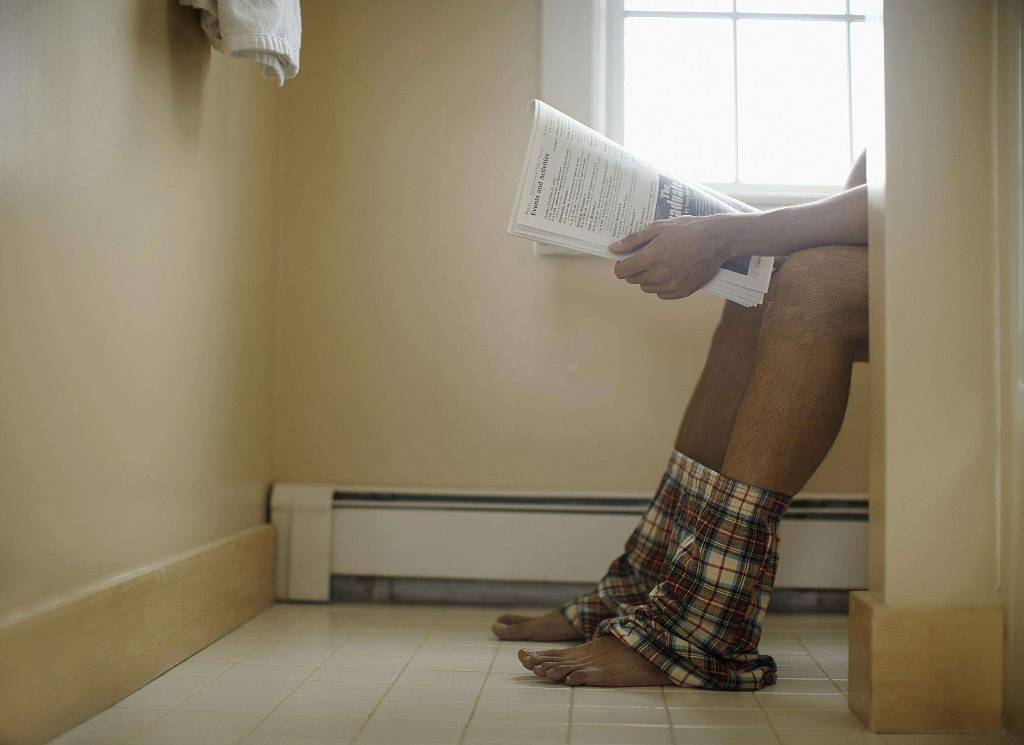 A man reading the paper on the toilet