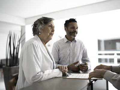 Mature men patient with female senior doctor on hospital reception
