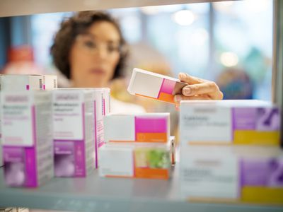 female physician looking at medications on shelf