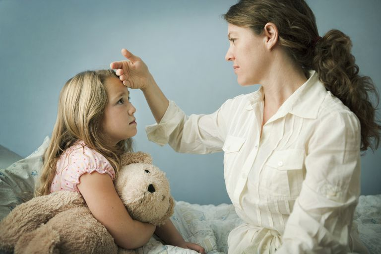 Mother checking 6 year old daughter for fever