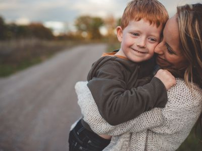 Mid adult woman carrying and hugging son on rural road