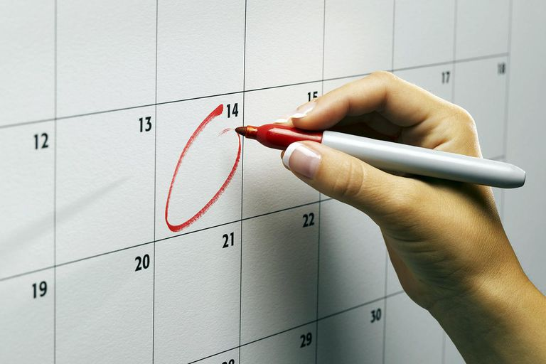 Woman circling day on wall calendar, close-up