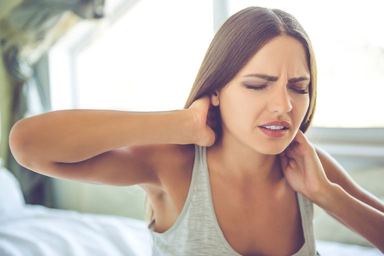 a woman waking up with neck pain