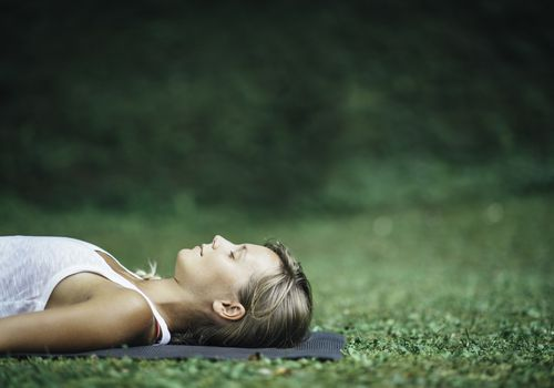 woman relaxing on a yoga mat outside