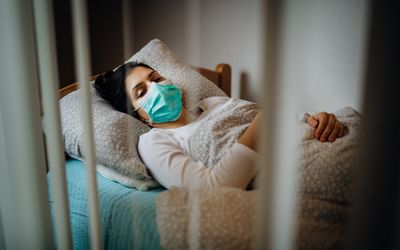 Woman wearing a face mask in a bed.