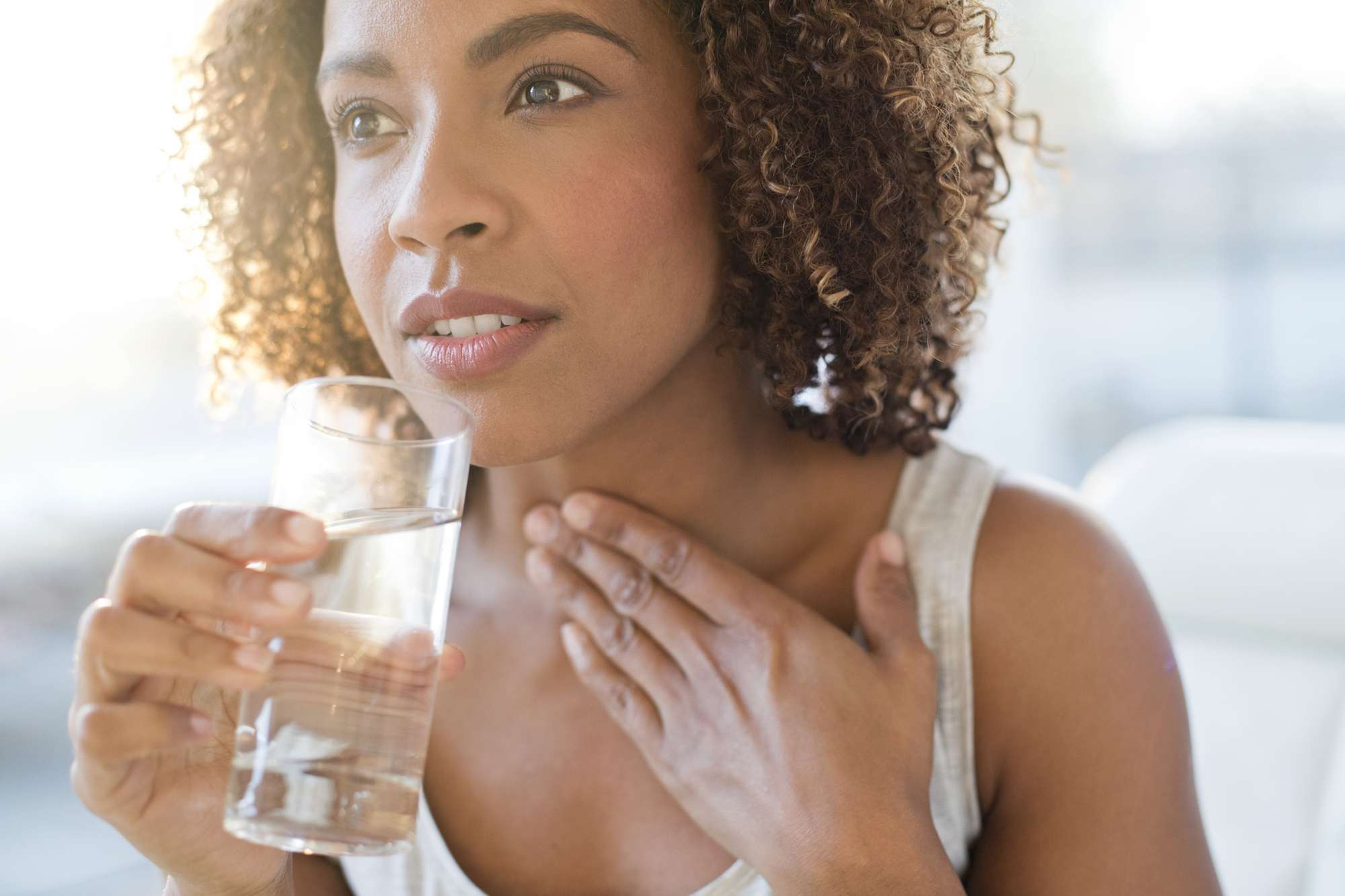 Woman with a glass of water and left hand on her throat