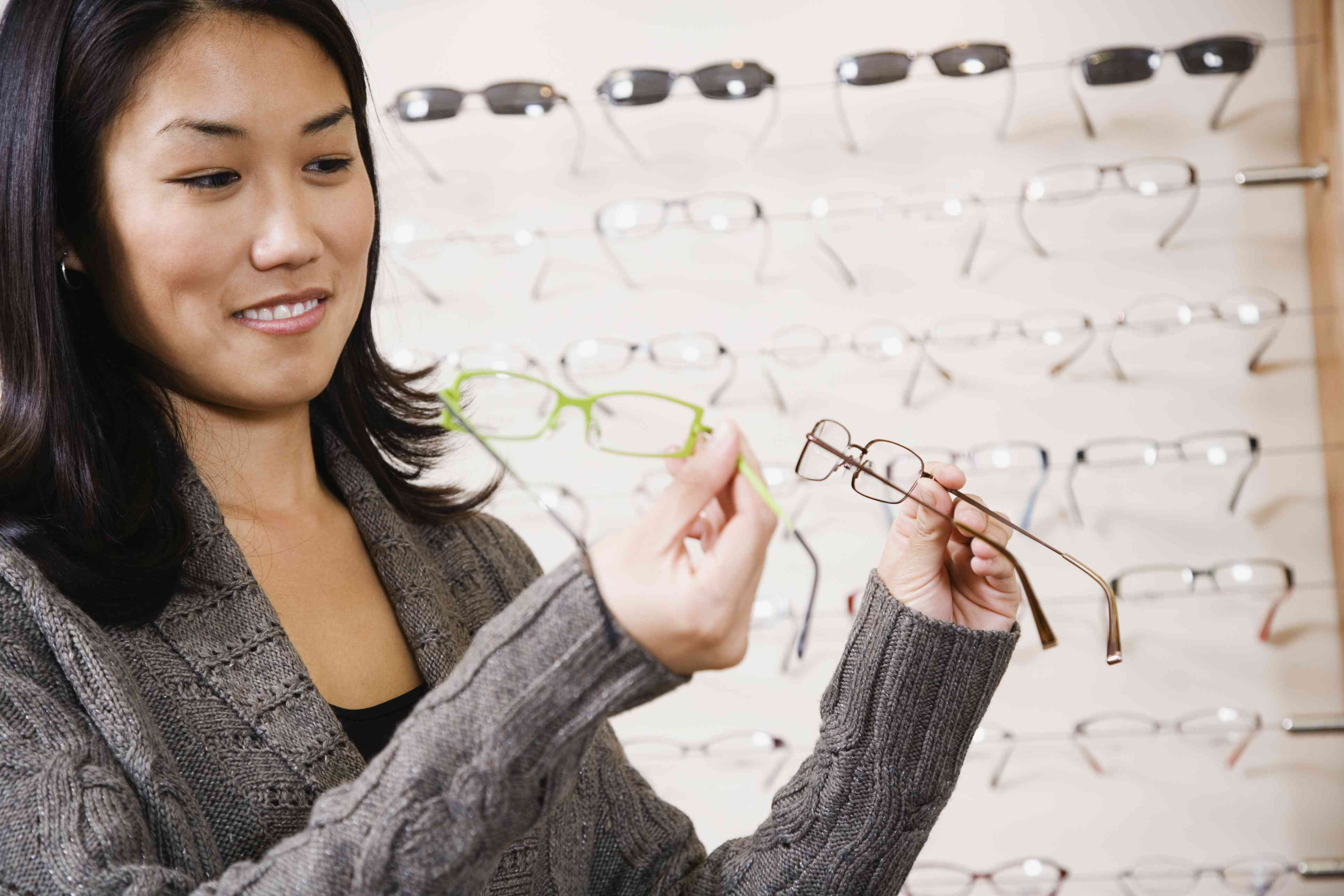 Woman looking at eyeglass frames in an optical store