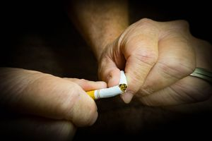 Cropped Image Of Person Breaking Cigarette