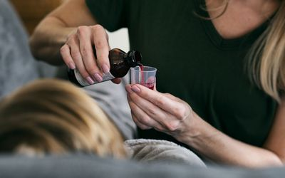 Mom pouring cough medicine for child