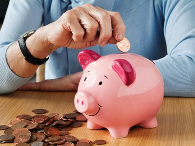 old woman filling piggy bank
