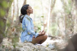 Woman meditating outdoors.