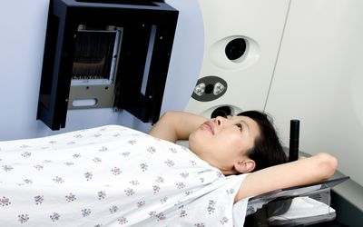 A woman undergoes breast cancer radiation therapy.