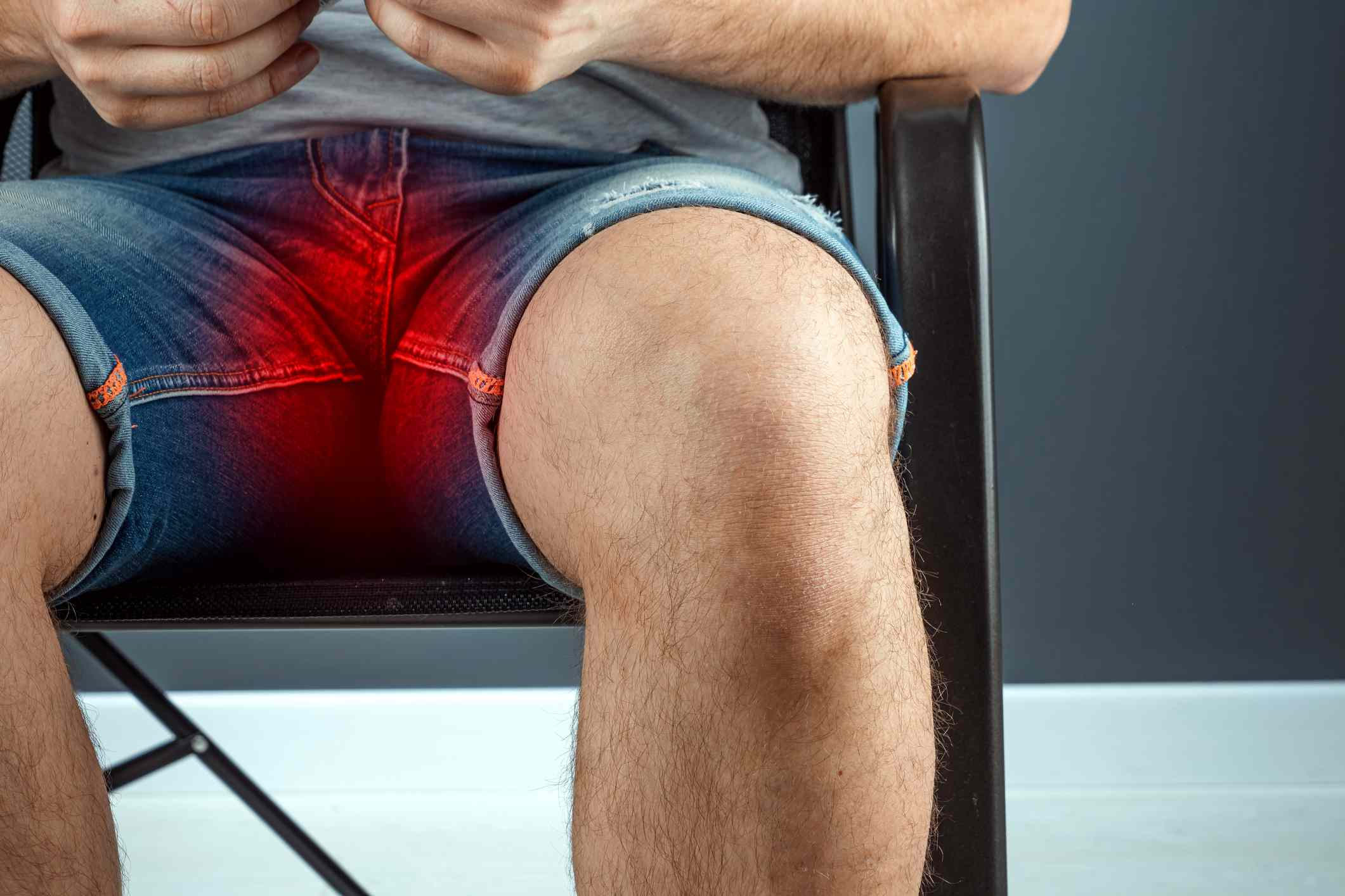 A close up of the pelvis of a man wearing jean shorts sitting on a chair. His groin is highlighted red.