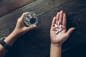 Cropped Hands Of Woman Holding Pills And Drinking Water In Glass