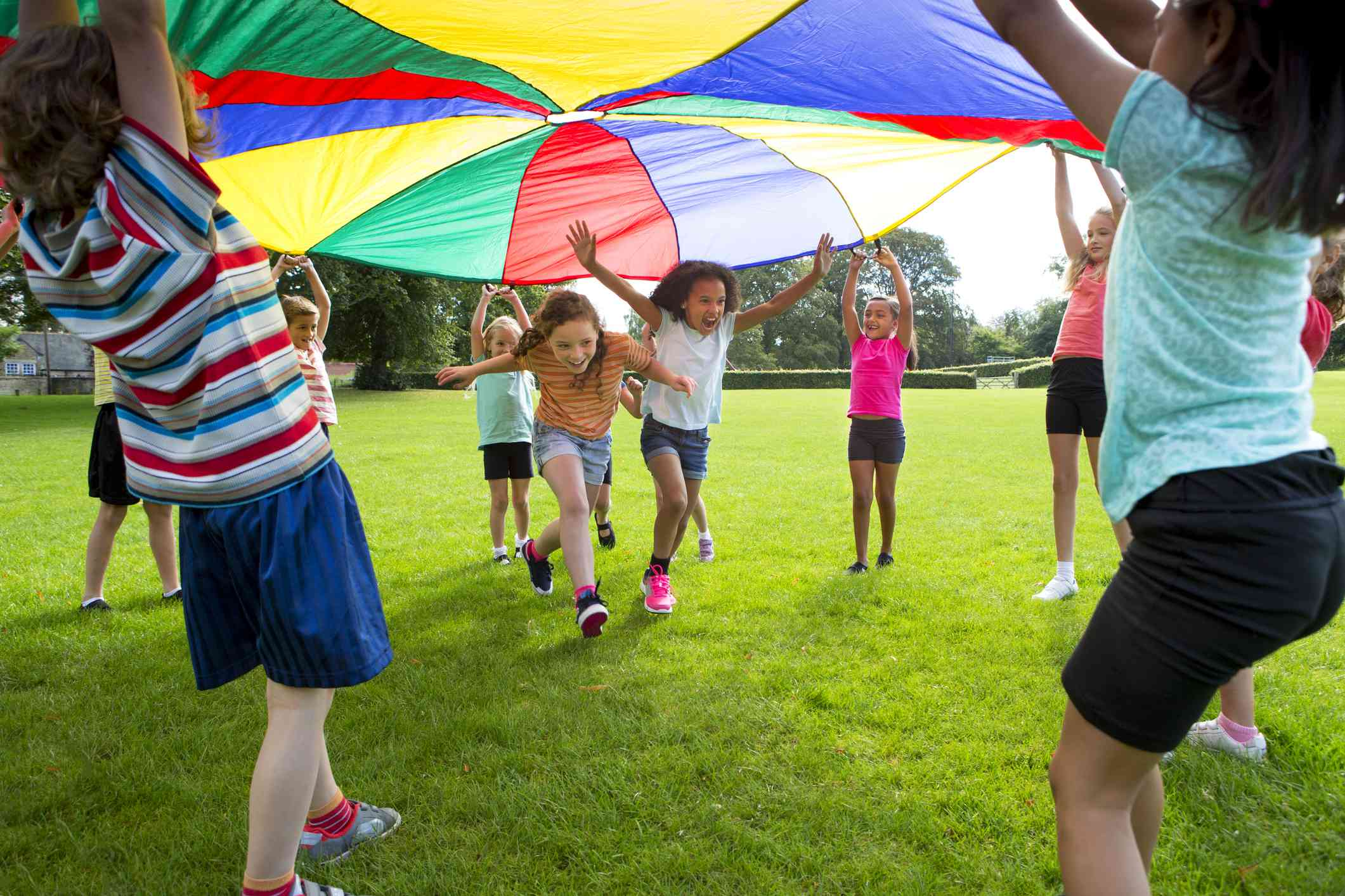 Children playing a game with a colorful parachute
