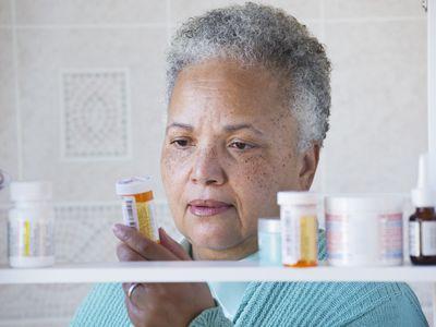 A woman examining her prescription bottles