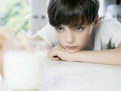Young boy looking at glass of milk
