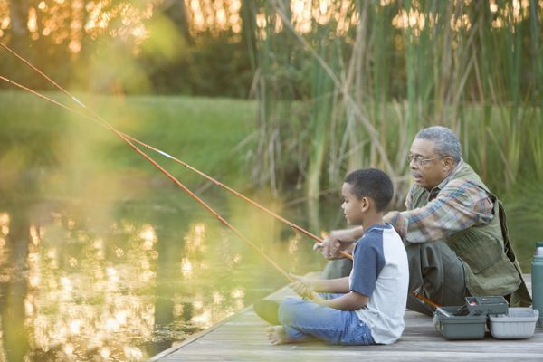 A grandfather and grandson sitting on a dock fishing