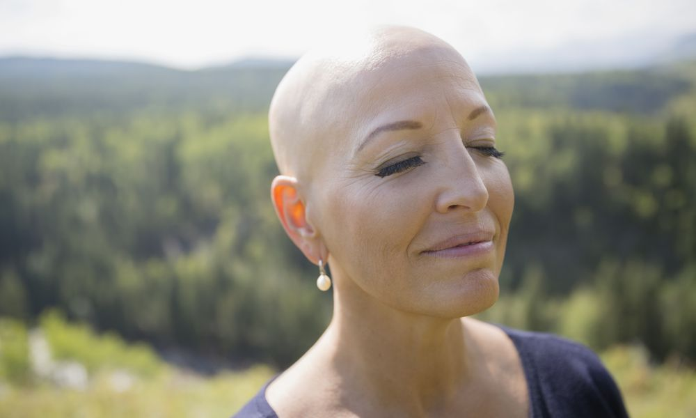 Woman with cancer smiling serenely outdoors