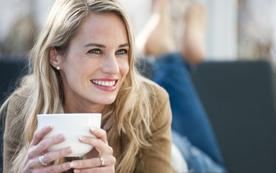 woman smiling, relaxing with a cup of tea
