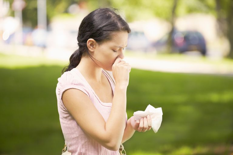Woman about to sneeze and holding a tissue outdoors in the sunshine