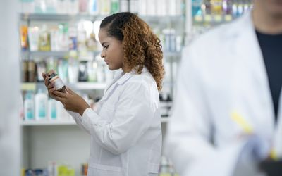 African female pharmacist working at pharmacy store, looking at medication -stock photo